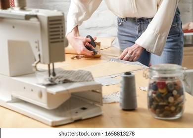 Seamstress cutting fabric with scissors. Fashion designer working with fabric in fashion studio.