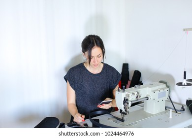 seamstress discuss work with boss using mobile, young pretty woman with ponytail sitting near table with cuttings in workshop and sewing machine talking on phone. Before receiving call female