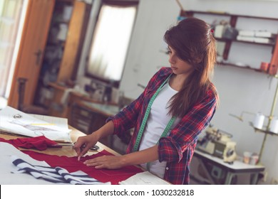 Seamstress drawing a T-shirt outline on a fabric with a piece of chalk