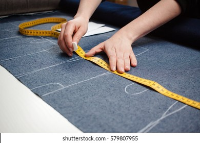 Seamstress hands on the work table with pattern and measuring tape.