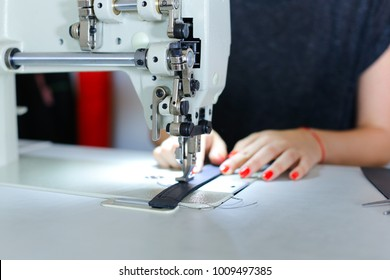 Seamstress sewing belt using sewing machine. Girl working at factory, female with red nails and bracelet sitting near table in workshop stitching black leather strap using special mechanism. Con