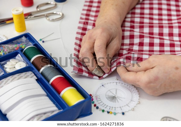 Seamstress sewing with needle and thread