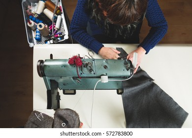 Seamstress sewing with a professional sewing machine. Top view.
