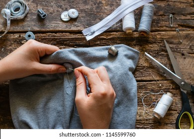 seamstress sews a button to clothes on a wooden background