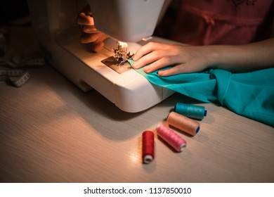 The seamstress sews clothes from the fabric on the sewing machine. Work with the light of the built-in hardware lamp. Steel needle with looper and presser foot close-up.
