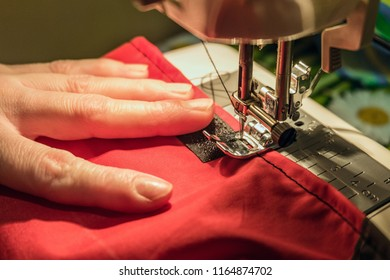 Seamstress sews clothes made of red cloth on a sewing machine. Work by the light of the built-in hardware lamp. Steel needle with looper and presser foot close-up.