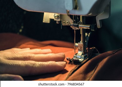 Seamstress sews clothes made of red cloth on a sewing machine. Work by the light of the built-in hardware lamp. Steel needle with looper and presser foot. Limited depth of field.