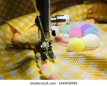 Seamstress sews clothes made of yellow cloth on a sewing machine. Work by the light of the built-in hardware lamp. Steel needle with looper and presser foot. Limited depth of field.