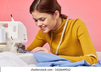 a seamstress sews clothes on a sewing machine
