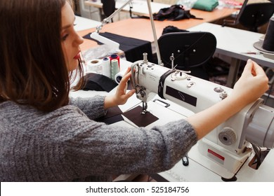 Seamstress tuning sewing machine for work. Young female tailor fixing stuck thread on her work equipment. Tailoring process, designer workplace, garment industry concept