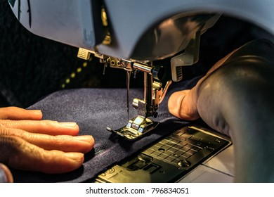 Seamstress work on the sewing machine. Night work by the light of the built-in hardware lamp. Machine sewing needle with looper and presser foot close-up.