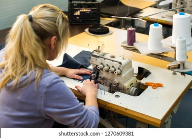 Seamstress or worker in textile factory sewing with industrial sewing machine