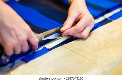 a seamstress works with cloth and scissors