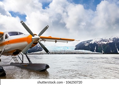 Seaplane or float plane in Alaska. The plane has landed under stormy skies near a glacier.