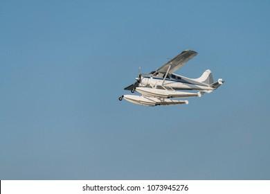 Seaplane, flying boat on clear blue sun sky background, side
