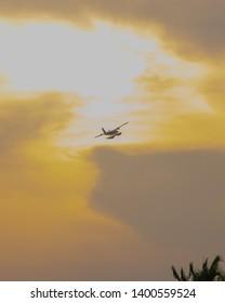 Seaplane flying in bright orange sky