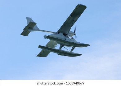 Seaplane (hydroplane or floatplane) flying in blue sky closeup. Cabin, wings propeller, engine, tail of plane are visible in details.