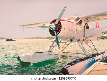 Seaplane moored on water with a propeller next to a jetty with the sun low in the sky behind causing a shimmer on the water