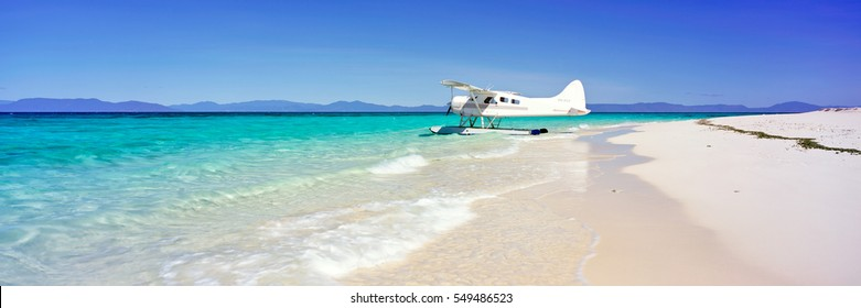 A seaplane on a white sand beach with blue water