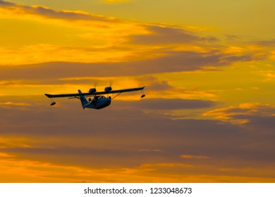 Seaplane with two propellers on the wings against the sky at sunset.