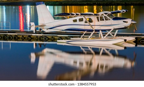 Seaplanes Tied up to a Wooden Floating Pontoon and Clear Sky. Small seaplanes tied up to a wooden floating pontoon on the shore of a mountain river. Vancouver, Canada.