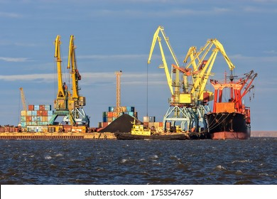 Seaport in the Arctic. A cargo ship near the pier of the sea port. Large port cranes. Logistics, shipping and freight in the Arctic. Stevedore services. Anadyr seaport, Chukotka, Far East Russia.