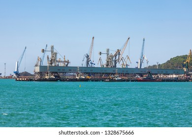 Seaport area, cranes loading ships in port, logistic import export business and transportation