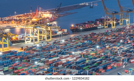 Seaport and loading docks at the port with cranes and multi-colored cargo containers day to night transition timelapse. Aerial top view from Montjuic hill after sunset. Barcelona, Spain