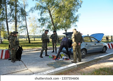Search at the checkpoint, military training. Man pulls his personal belongings out from a car, soldiers stand around watching. October 18, 2018. Novo-Petrivtsi military base, Ukraine