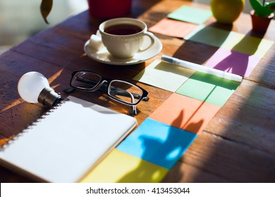 Search creative concepts. Notebook, glasses, postits and a lamp on a wooden table. Morning light.