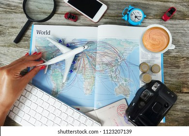 Search flight tickets online with woman looking for travel destination on map surrounded by travel objects