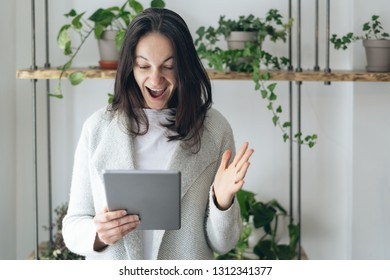 Search and found concept. Photo of exited lady with tablet in hands standing inside co working or restaurant space. She making happy face with wide open mouth