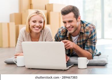 In search of a good moving company. Cheerful young couple laying on the floor of their new apartment and looking at laptop while cardboard boxes laying in the background