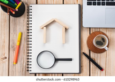 Search For House or Flat, Real Estate Concept On Work Desk With Notebook And Magnifying Glass