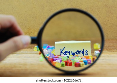 Search for keyword concept. Magnifier and colorful alphabet on wooden background.