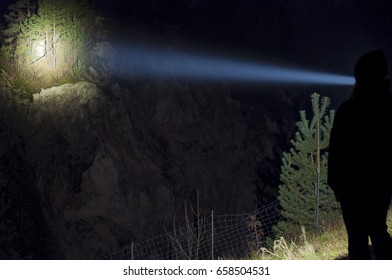 Search light shining on a hill side with trees and small quarry