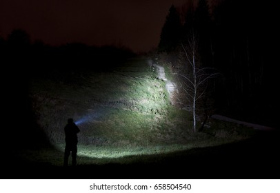 Search light shining on a hill side with trees and steps