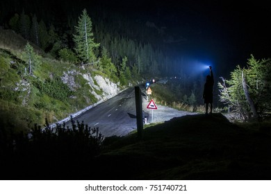 Search light shining on a mountain road, high position