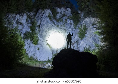 Search light shining on a quarry with trees