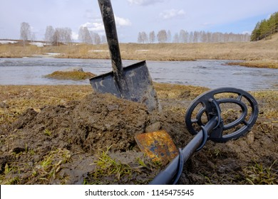 search for metal things in the ground, metal detector outdoors in the forest, dug up earth and shovel in the mud