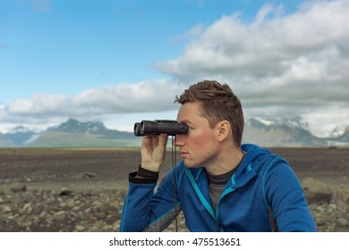 In search of new emotions and impressions. Man looking through binoculars at mountains landscape in Iceland.