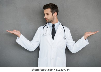 In search of right medical solution. Handsome young doctor in white uniform stretching out his arms while standing against grey background