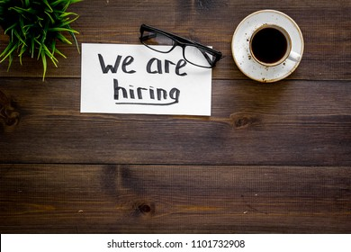 Search for worker, employee concept. We are hiring lettering on work desk on dark wooden background top view copy space