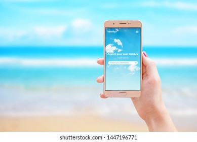 Search your next holiday travel app on smart phone in woman hand. The concept of using the internet and apps for finding destinations and booking tickets and accommodation.