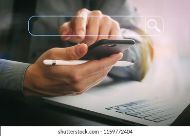 Searching Browsing Internet Data Information Networking Concept with blank search bar.businessman working with mobile phone and stylus pen and laptop computer on wooden desk in modern office