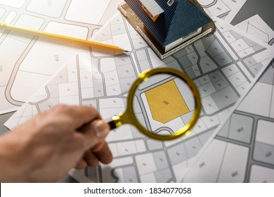 searching building plot for family house construction - hand with magnifier on cadastre map - Shutterstock ID 1834077058