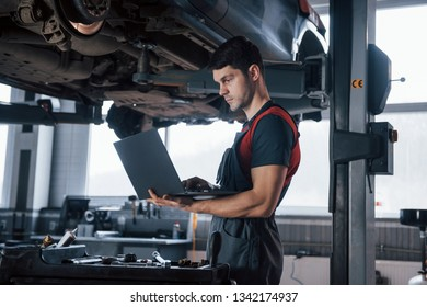 Searching for details in internet. Man at the workshop in uniform using laptop for his job for fixing broken car.