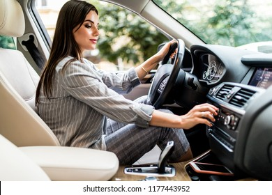 Searching for favorite music. Young woman smiling and pushing buttons while driving a car
