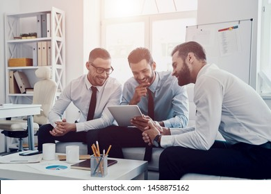 Searching for fresh ideas together. Group of young modern men in formalwear working using digital tablet while sitting in the office