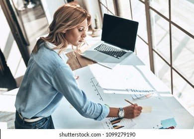 Searching for fresh ideas. Top view of young woman writing something down on the blueprint while working in the creative office